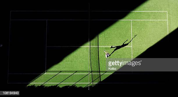 Aerial shot of tennis match from above with player's shadow