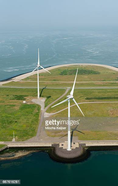 aerial shot of two wind turbines mounted on the oosterschelde flood barrier, vrouwenpolder, zeeland, netherlands - zeeland stock pictures, royalty-free photos & images