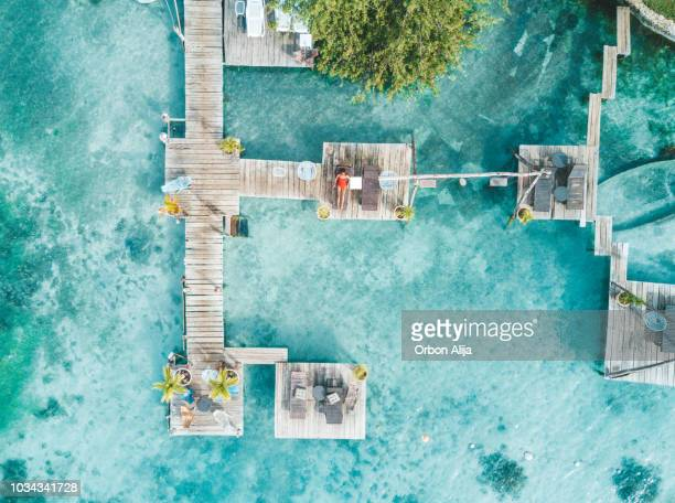 aerial shot of woman relaxing in a water bungalow - maldives stock pictures, royalty-free photos & images
