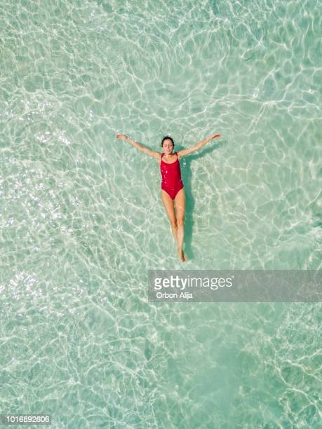 aerial shot of woman relaxing in the beach - standing water stock pictures, royalty-free photos & images