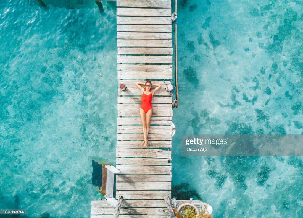 Aerial shot of womann relaxing in a water bungalow : Stock Photo
