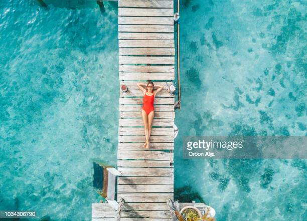 aerial shot of womann relaxing in a water bungalow - clima tropicale foto e immagini stock