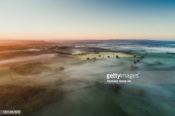 aerial shot showing a low level mist at sunrise over the english countryside, england, united kingdom - weather stock pictures, royalty-free photos & images