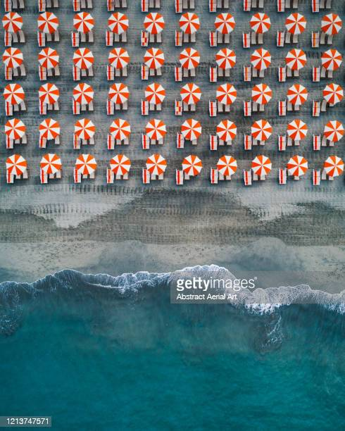 aerial shot showing rows of beach umbrellas at the edge of the ocean, tuscany, italy - kustlijn kust karakteristiek stockfoto's en -beelden