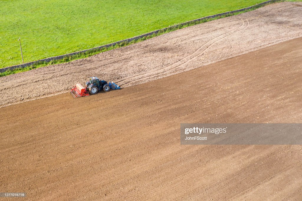 Aerial side view of a tractor being used to pull a seed drill on a Scottish farm on a late summer day : Stock Photo