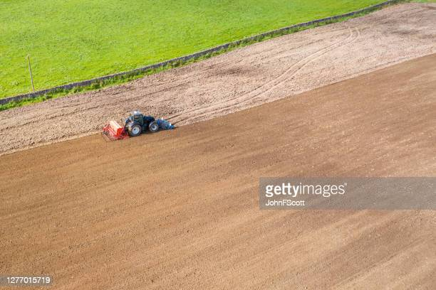 aerial side view of a tractor being used to pull a seed drill on a scottish farm on a late summer day - johnfscott stock pictures, royalty-free photos & images