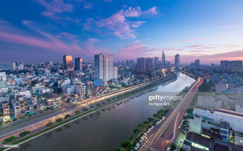 Aerial sunset view of houses and Business and Administrative Center of Ho Chi Minh city on NHIEU LOC canal : Foto de stock