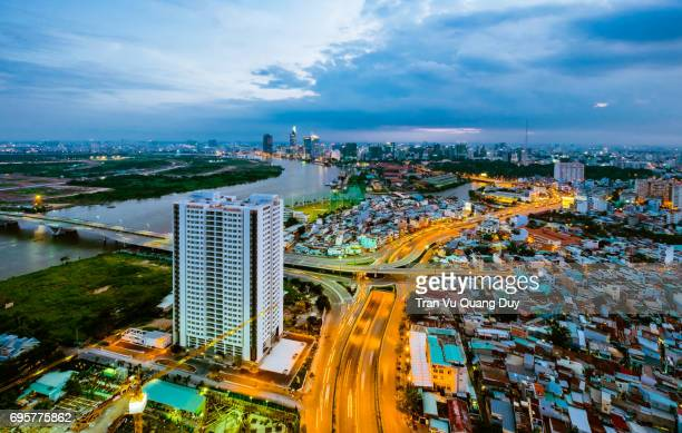 aerial sunsetview of colorful and vibrant cityscape of downtown in ho chi minh city with thu thiem bridge cross the river and skyline of saigon - thiem stock-fotos und bilder