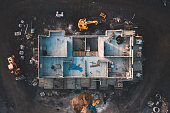 Aerial top down shot of a house frame on a construction site surrounded by mud