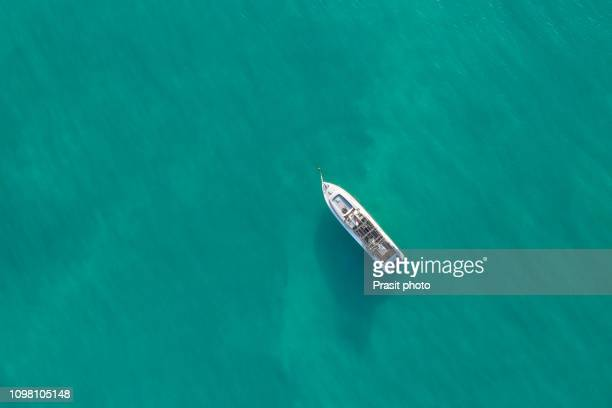 aerial top shot of a luxurious yacht on the sea - yacht stock pictures, royalty-free photos & images