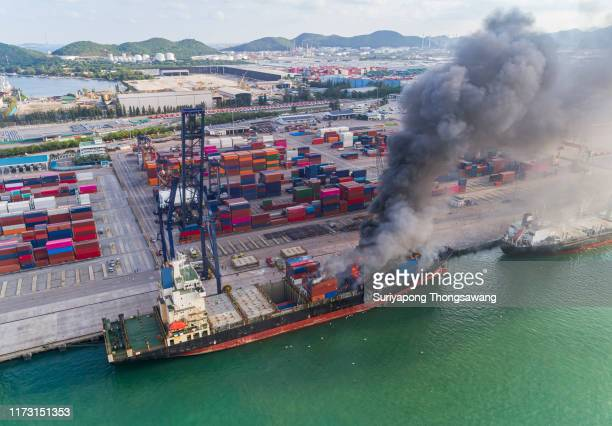 aerial top view container ship at sea port and working crane bridge loading container for logistics, import export, shipping or transportation. - being fired photos stock pictures, royalty-free photos & images