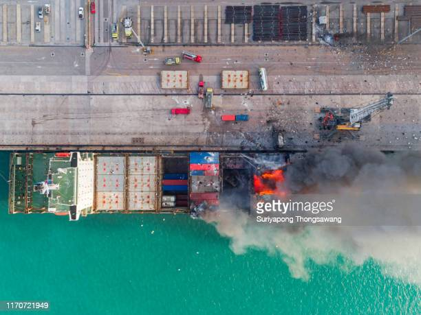 aerial top view container ship be on fire at sea port for accident logistics, import export, shipping or transportation. - being fired photos stock pictures, royalty-free photos & images