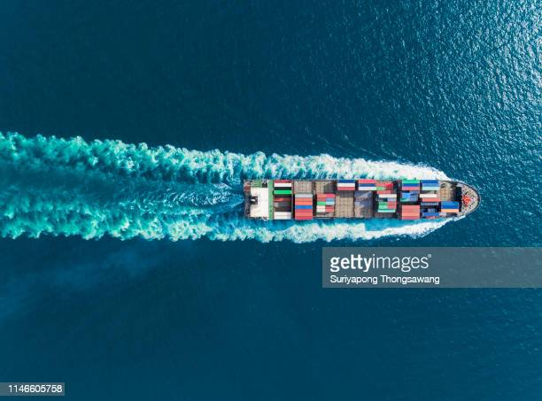 aerial top view container ship full speed with beautiful wave pattern for logistics, import export, shipping or transportation. - cargo ship stock pictures, royalty-free photos & images