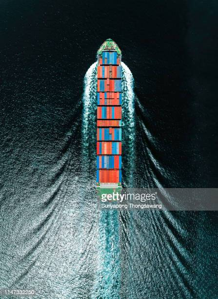 aerial top view container ship on deep sea full speed with beautiful wave pattern for logistics, import export, shipping or transportation. - container stock-fotos und bilder