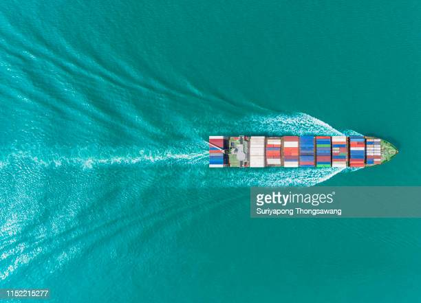 aerial top view container ship on the green sea full load container for logistics, import export, shipping or transportation. - schiffsfracht stock-fotos und bilder