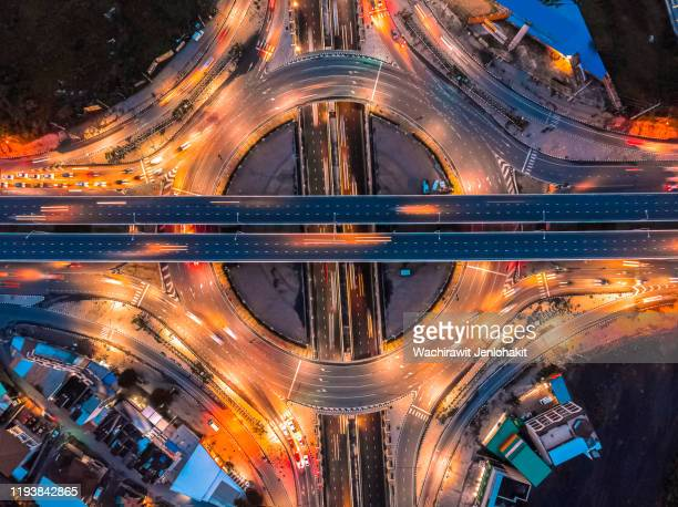 aerial top view, highway road roundabout intersection or circle at night for transportation that facilitates the travel of car users on the road transportation or futuristic concept. - futuristic car stock pictures, royalty-free photos & images