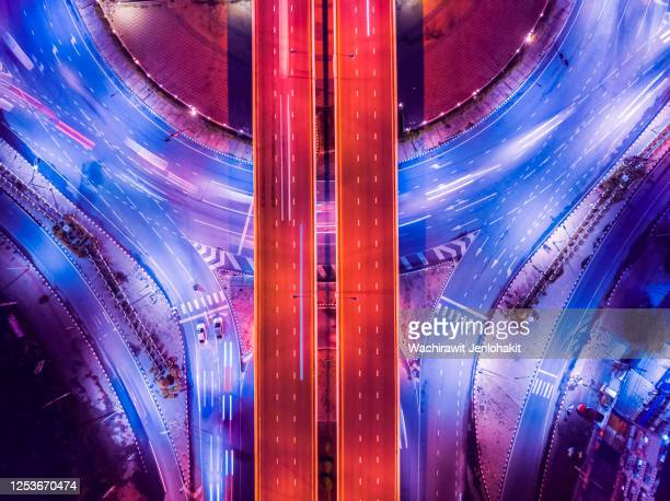 aerial top view, highway road roundabout intersection or circle at night for transportation that facilitates the travel of car users on the road transportation or futuristic ( colorful ) concept. - lightweight stock pictures, royalty-free photos & images