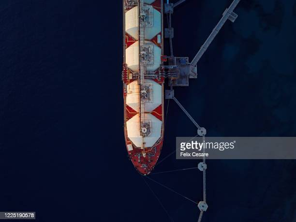 aerial top view of a liquefied natural gas (lng) tanker moored to the jetty - 液化天然ガス ストックフォトと画像