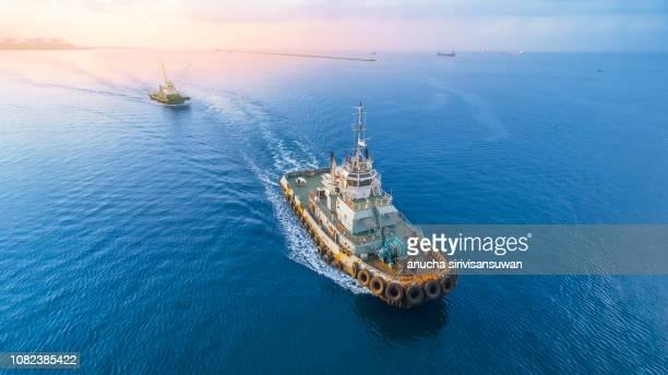 aerial top view of cargo ship, two tug drag container in warehouse harbor at thailand . - industrial sailing craft stock pictures, royalty-free photos & images