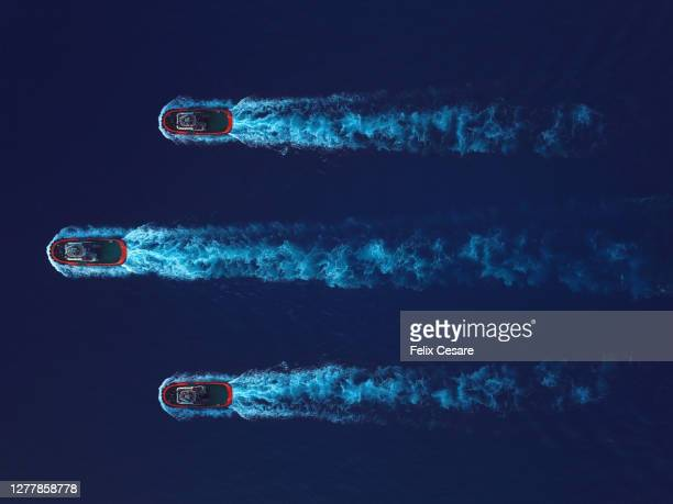 aerial top view of three tugboat on the move surrounded by deep blue water. - three objects stock pictures, royalty-free photos & images