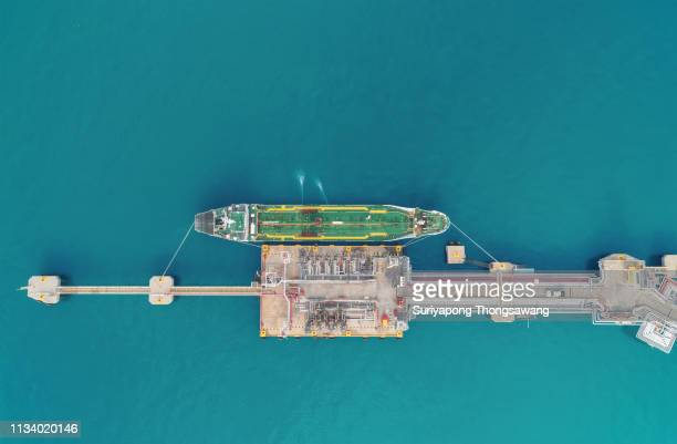 aerial top view oil ship tanker loading oil at ship's bridge from refinery for transportation. power or energy concept - motor oil stock pictures, royalty-free photos & images