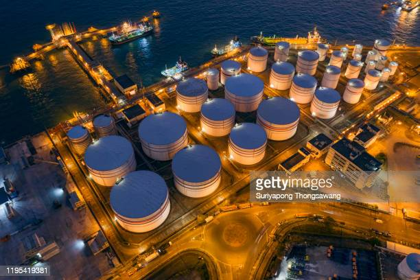 aerial top view oil tanker warehouse with loading dock on the sea at night. - danger stock pictures, royalty-free photos & images