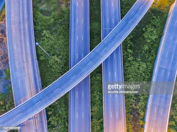 aerial top view road 4 way on tree background at twilight. - single track stock pictures, royalty-free photos & images