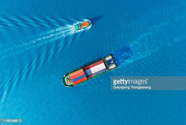 aerial top view small container ship on the blue sea for logistics, import export, shipping or transportation. - schip watervaartuig stockfoto's en -beelden