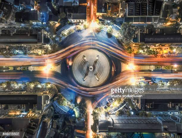aerial top view traffic circle with speed light in city at night , democracy monument , bangkok , thailand . - capital cities stock pictures, royalty-free photos & images