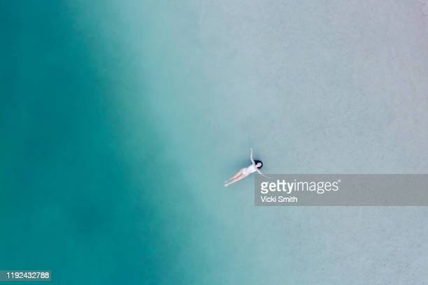 aerial view above a woman lying, floating in the shallow water of the ocean - gold coast queensland stock pictures, royalty-free photos & images
