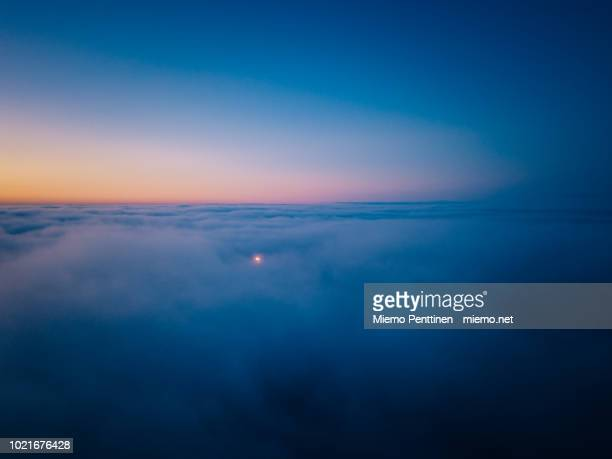aerial view above the clouds at dusk, with flame from an oil refinery pushing through the clouds - avondschemering stockfoto's en -beelden