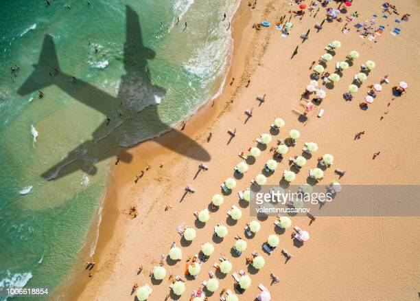 aerial view airplane shadow and beach with umbrellas - helicopter photos stock pictures, royalty-free photos & images