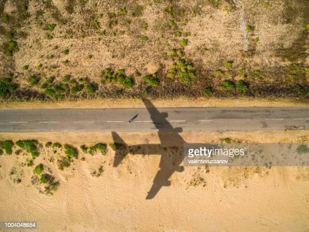 aerial view airplane shadow and man on sunny road - climate stock pictures, royalty-free photos & images