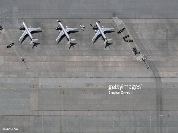 aerial view airplanes parked on tarmac at airport - ponto de vista de drone - fotografias e filmes do acervo