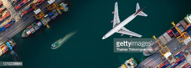 aerial view and top view cargo plane flying above ship port in the export and import business and logistics international goods. shipping cargo to harbor by crane - transport stock pictures, royalty-free photos & images