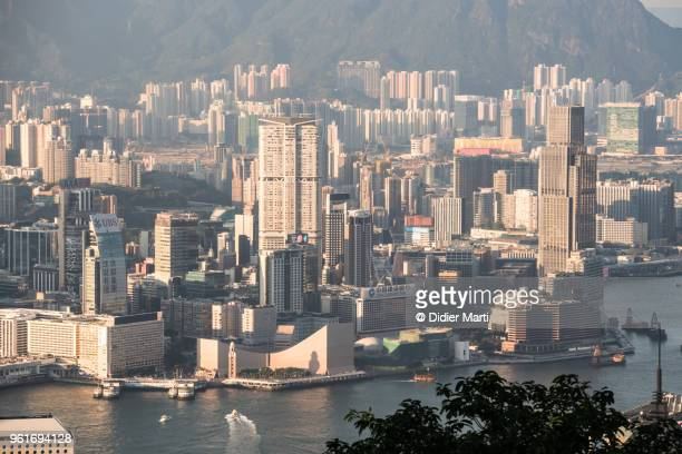 aerial view at sunset of the waterfront skyline of kowloon in tsim sha tsui in hong kong from across the victoria harbour - tsim sha tsui stock pictures, royalty-free photos & images