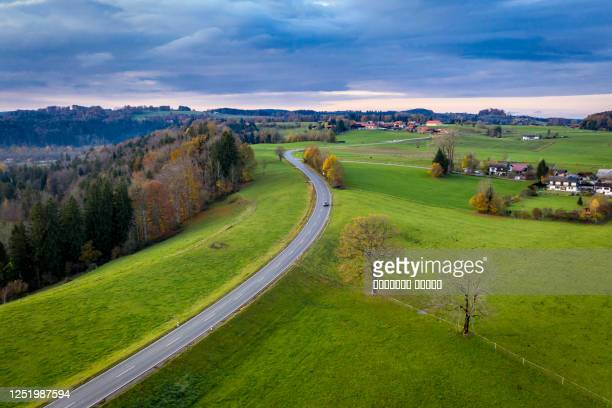 aerial view autumn landscape in bavaria near miesbach. road going into the distance and the peaks of the alps on the horizon. clouds sky, yellow trees and green field - ländliches motiv stock-fotos und bilder