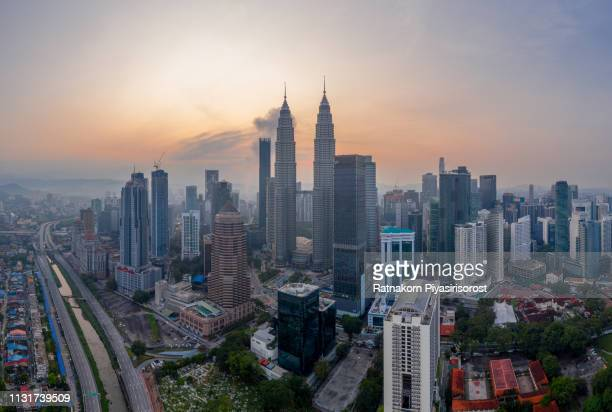 aerial view cityscape of kuala lumpur, malaysia at dawn, with illuminated petronas towers and communication tower in the distance. - kuala lumpur photos et images de collection