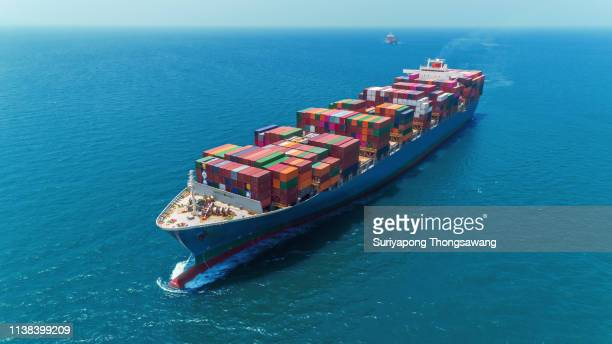 aerial view container ship full load container delivering on the blue sea for logistics, import export, shipping or transportation. - cargo ship stock pictures, royalty-free photos & images