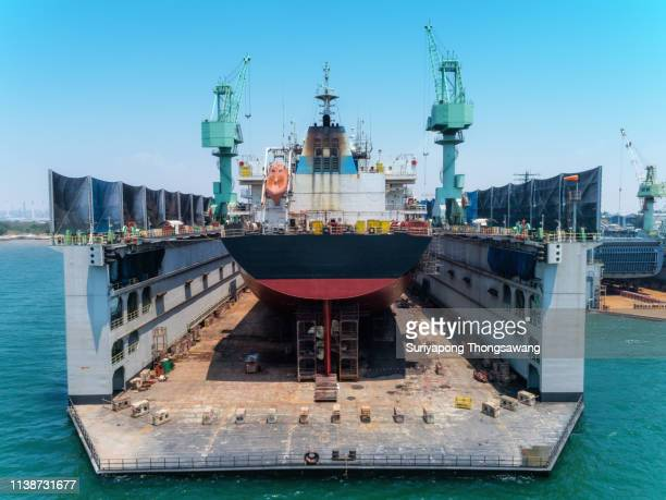aerial view container ship repairing in shipyard for shipping industry , import export or transportation. - shipyard stock pictures, royalty-free photos & images