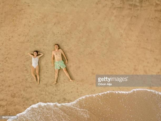 par de vista aérea en la playa - lying down fotografías e imágenes de stock
