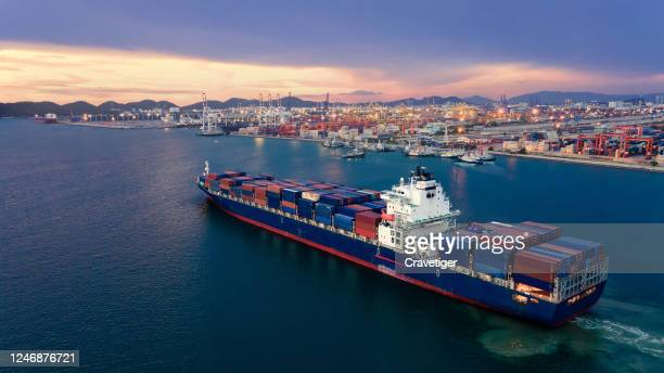 aerial view drone shot of a massive vessel in dock at the port of thailand, full of multicoloured shipping containers. boat 're going to push and pull ship with container to deep sea. - harbour stock pictures, royalty-free photos & images