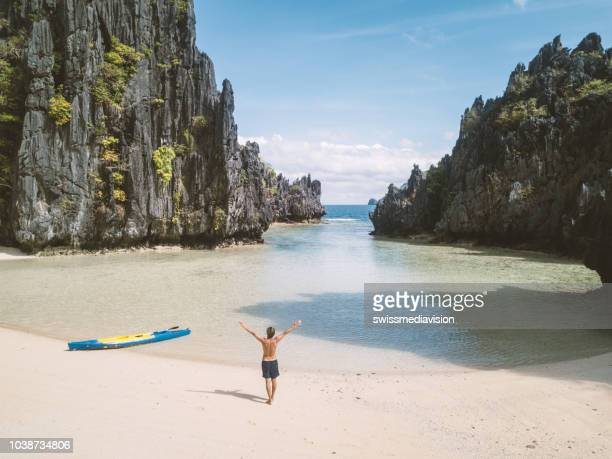 aerial view drone shot of a young man standing on idyllic lagoon beach arms wide open near canoe enjoying freedom life and happiness.  el nido, palawan - palawan stock pictures, royalty-free photos & images