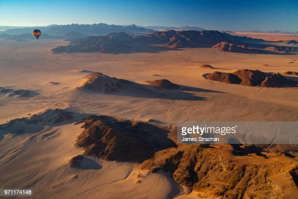 aerial view from a balloon of another balloon cruising over the sossusvlei area at dawn, namib desert, namib-naukluft, namibia (property release) - james strachan stock pictures, royalty-free photos & images