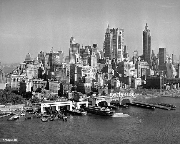 Aerial view from the East River looking northwest of the financial district and east side skyline of lower Manhattan New York New York mid 1960s...