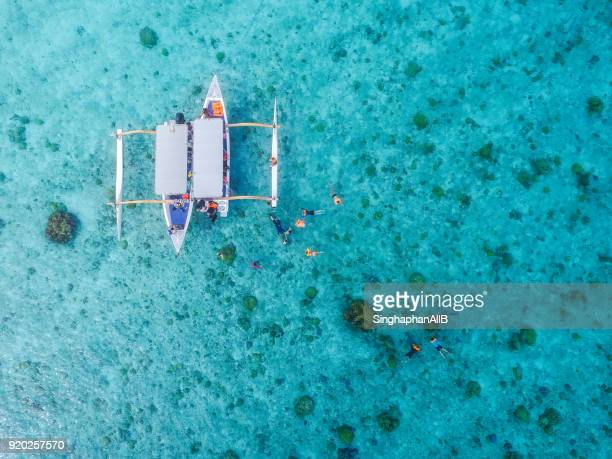 aerial view from top of traditional boat Bora bora and diving tourists