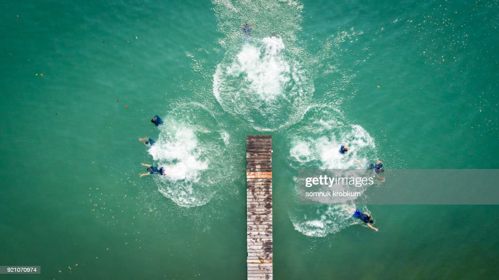Aerial view jumping boy into clear sea water in summer by drone : Stock Photo