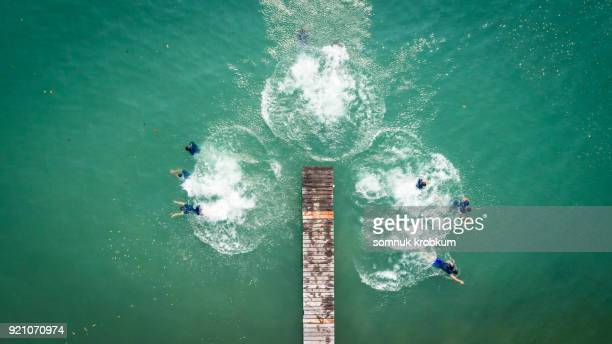 Aerial view jumping boy into clear sea water in summer by drone