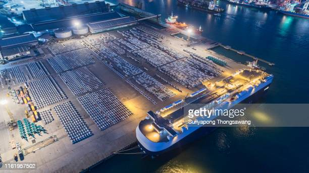 aerial view large roro (roll on/off) carrier vessels loading cars and trucks at quayside into and out of the world market. - carrying stock pictures, royalty-free photos & images