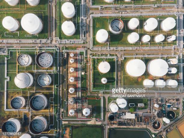 aerial view morning time of petro chemical plant and oil refinery, power plant working with crude oil storage tank at sunrise near mountain green environment concept - factory stock pictures, royalty-free photos & images